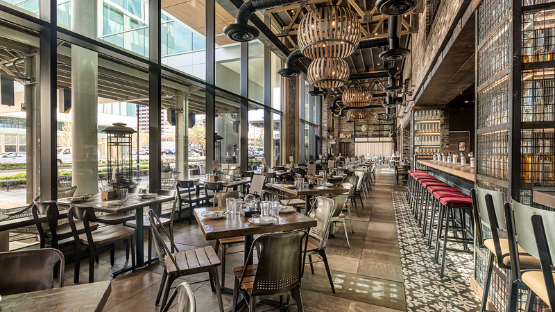 The Grotto Restaurant in downtown houston texas, a rustic old world feel with tables lined up on a glass wall. to the right are barstools where you can sit and have pizza right out of a pizza oven.
