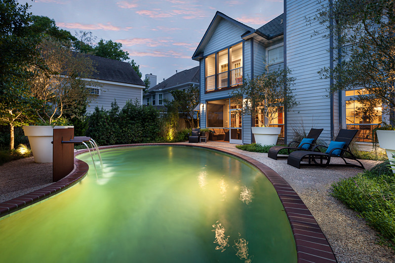 Twilight Pool landscape with cokebottle green water to mimic the texas hill country. giant sized white landscape tree pots and a steel water feature.