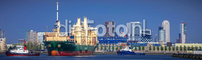 Sleepboot voor boeg zeeschip met Rotterdam op achtergrond