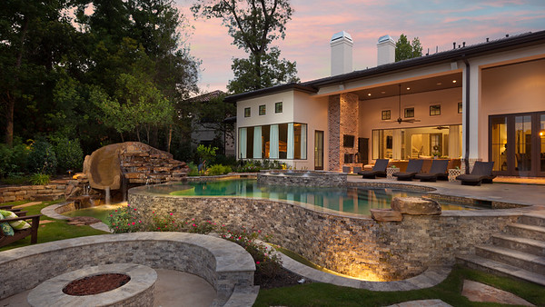Carltonwoods backyard landscape, pool and cement slide with firepit and beautiful landscaping