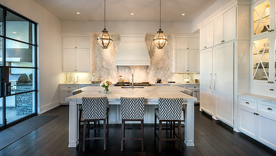 Large White Kitchen, globe pendant lights over a large island with geometric printed fabric, to the right is a china display with glass cabinet doors. dark wood floors give this room beautiful contrast.