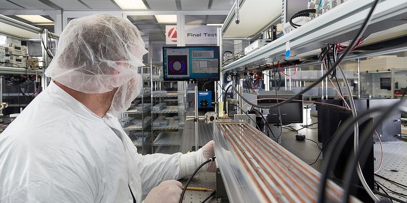 Engineer calibrates laser.