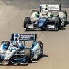 This image was taken at the Mid Ohio race course during the Indy Car race.<br /> Here, Helio Castroneves is seen checking his mirrors as he attempts to fight off his pursuer.  <br /> <br /> This image is sized at 2x3 and can be seen in the Game Shots gallery.