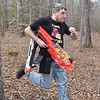 """(Brad Davis/The Register-Herald) Nerf soldier Ross Jones, 34, rushes back into the fight after having to go all the way back to his team's starting point to """"respawn"""" after being hit Saturday at Lake Stephens."""