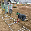 (Brad Davis/The Register-Herald) Crew members Devin Dempsey, left, and Drew Maxey begin building the starting line area as they and others prepare a moto-cross dirt track inside the Beckley-Raleigh County Convention Center in preparation for the Tristate MX Indoor Championship Series Thursday afternoon. Running tonight and Saturday at 7:00 p.m., the two-night dirt bike racing event is open to area participants of all ages and classes including beginner and youth, with proper gear and their own dirtbikes required. Sign-ups will begin today at the Convention Center at 10:00 a.m. and on Saturday at 9:00 a.m. This will be the first of four events for the Huntington-based series, which will travel to Lexington, Kentucky for their next event two weeks after this. Potential riders will be checked for safe equipment and asked to sign waivers.