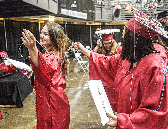 F. Brian Ferguson/Register-Herald  Chelsea Jones, left, gets help from her classmates removing streamers from her hair moments after the Liberty High School Commencement at the Beckley-Raleigh County Convention Center.