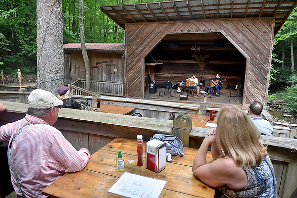 (Brad Davis/The Register-Herald) Hurricane resident Mike Shawler, left, and St. Albans resident Shawn McQuinn relax at a table as they take in a performance by Lewisburg musician Jim Snyder (left on stage with fellow musician Jim Hughes) and a handful of others during a day of tunes and hanging out at the Chimney Corner Cafe & Amphitheater Sunday afternoon near Ansted. Shawler is a musician himself and was one of the artists on hand performing throughout the day.