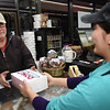 Mike Ross, of Beckley, buys a box of donuts from Preshma Dhakal at the Donut Connection<br /> (Rick Barbero/The Register-Herald