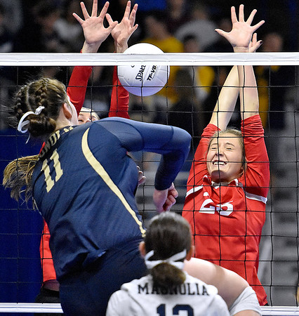 (Brad Davis/The Register-Herald) Greater Beckley Christian's Nevaeh Dickens, right, and Courtney Green step up to block as Magnolia's Madelyn Winters spikes the ball during State Volleyball Tournament action Friday evening at the Charleston Civic Center.