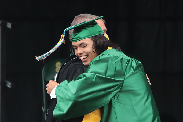 Malachi Crews hugs Principal Ben Routsen after receiving his diploma from Greenbrier East High School at the 52nd Annual Commencement ceremony in Fairlea Friday. Jenny Harnish for the Register-Herald