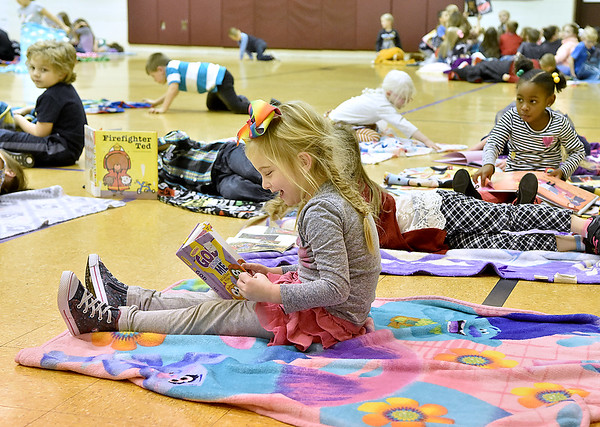 (Brad Davis/The Register-Herald) Crescent Elementary School students cozy up with blankets and read during the school's Read-a-Thon fundraiser Wednesday afternoon. The event was a different take on fundraising where every child got sponsors and collected donations in the hopes of raising a combined $5,000 towards playground equipment and other support items. Participating students then gathered Wednesday in the gym with a pillow and blanket to cozy up with as they read and were read to by their teachers.
