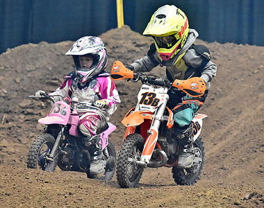 (Brad Davis/The Register-Herald) Young racers Blaze Wolfe (#13b), 6, and Cailyn Adkins, 5, motor through a section of the course as they compete in the 50cc four through eight-year-old division during the weekend's Tristate MX dirt bike racing event Saturday night at the Beckley-Raleigh County Convention Center.