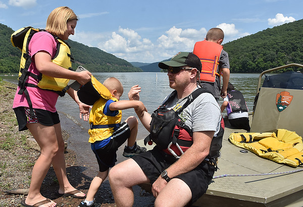 (Brad Davis/The Register-Herald) National Park Service River Ranger Kip Conklin assists as Lerona residents Collin Hill (right), 7, his little brother Easton, 5, and their mother Megan, among other passengers board prior to a boat ride on Blustone Lake Sunday afternoon.