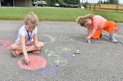 (Brad Davis/The Register-Herald) Six-year-old Madison Delp, left, and Autumn Colombo, 5,draw in chalk on the pavement during Grandview Christian Church's Wacky Wednesday outdoor activity event at their property in Grandview where the old drag strip is.