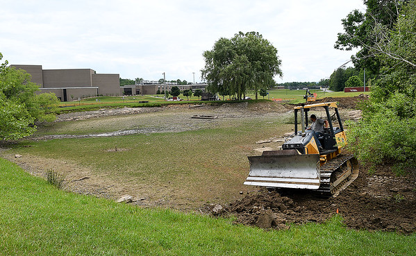 Crew with All-Con, LLC from Beaver, work on a water quality enhancement project at Woodrow Wilson High School pond. The pond had dangerous levels of fecal bacteria and they are fixing the issue by restoring it to a natural wetl;and condition.<br /> (Rick Barbero/The Register-Herald)