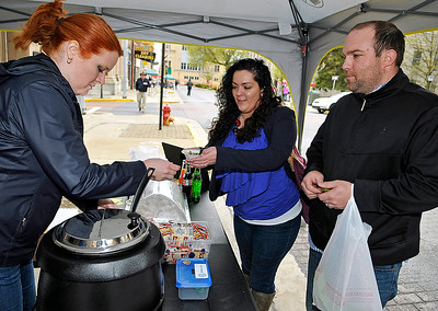 """Brad Davis/The Register-Herald Prosperity residents Tanairi Airey and her husband Kyle get themselves a second helping of Fa. So. Latte's """"Italian Wedding"""" soup from co-owner Michele Davis, left, during Souper Saturday activities yesterday evening in downtown Beckley."""