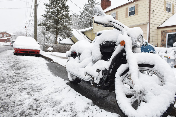 Snow covered up a motorcycle on Westwood Drive after the area got hit with 4 inches of snow early monday morning.<br /> (Rick Barbero/The Register-Herald)