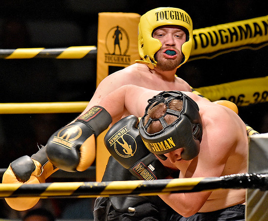 (Brad Davis/The Register-Herald) Hinton's James Raines, yellow, takes on Lester's Jarrett Cochran in a heavyweight matchup during the Original Toughman Contest Friday night at the Beckley-Raleigh County Convention Center. Raines would win the fight.