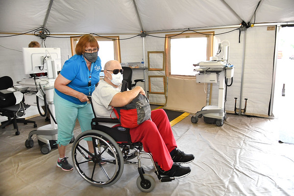 Amelia Chen, volunteer, left, wheels Jackson Hart, of Danese inside the Beckley VA Medical Center.<br /> (Rick Barbero/The Register-Herald)