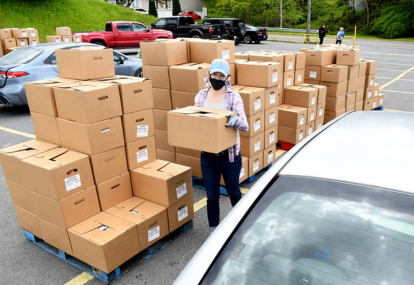 Amanda Hammons, volunteer, load boxes of food during Farmers to Families food giveaway held Friday from noon until 4 p.m. at the Beckley-Raleigh County Convention Center. 1200 boxes of food that was supplied contain fresh produce, meat and dairy products.<br /> (Rick Barbero/The Register-Herald)