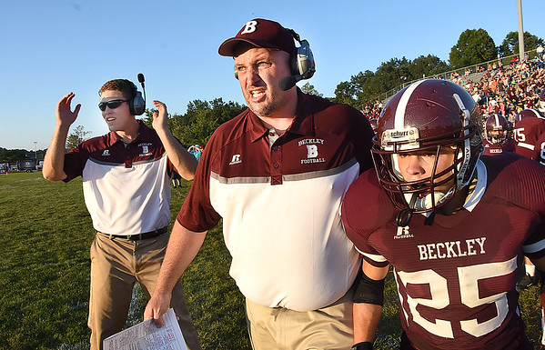 Woodrow Wilson head coach Chad Sarrett, center, gives instructions to Noah Norman, right, during game against Riverside High School at Van Meter Stadium in Beckley Friday night. (Rick Barbero/The Register-Herald)