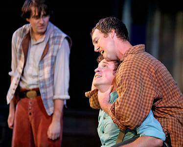 Brad Davis/The Register-Herald    Tolbert McCoy (right), played by Jason Adkins, holds Johnse Hatfield, played by Benjamin Stoll, in a headlock as Phamer McCoy (far left background), played by Beckley's Nick Yurick, watches with joy during a scene from Theatre West Virginia's Hatfields and McCoys in which the three elder McCoy sons rough up the romancing Hatfield during a fight July 25 at Grandview Park's Cliffside Amphitheatre.