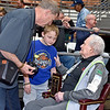 (Brad Davis/The Register-Herald) Cobel resident Justin Miller, left, introduces his 9-year-old grandson Corey Hall to Lewis D'Antoni during the Scott Brown memorial game Saturday evening at the Beckley-Raleigh County Convention Center. Miller, a 1965 graduate of Mullens High School said the now 103-year-old D'Antoni was the last person who ever whipped him. His grandson Corey is multi-sport athlete who attends Herndon Consolidated and says basketball is his favorite.