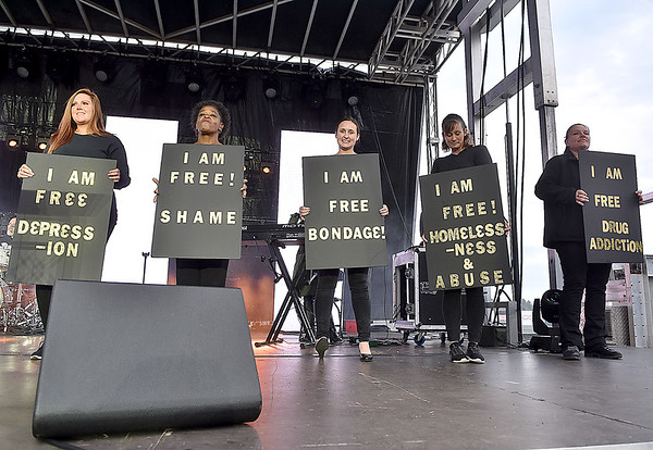 (Brad Davis/The Register-Herald) Participants take the stage carrying signs stating what they overcame in their lives at the conclusion of a performance from musician and pastor Judy Jacobs, one of many activities taking place during the first I Am Ingathering all-day event Saturday afternoon at Linda K. Epling Stadium.
