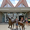 (Brad Davis/The Register-Herald) Shoppers check out the sculptures and other art works outside of Tamarack Friday afternoon.