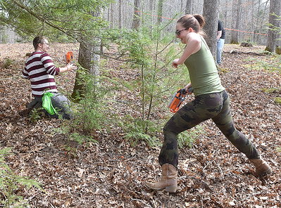 (Brad Davis/The Register-Herald) Teammates Cole Bird (left), 29, and Emily Cox, 15, scramble for cover as attackers converge on them during an all-ages Nerf battle for Lake Stephens Saturday afternoon.