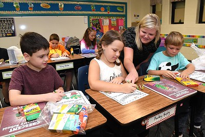 Kattie Cooper, third grade teacher Crescent Elementary School in Beckley, third from left, works with her new students, Joey DellaMea, left, Audrey Murphy and Ethan Scott, during the first day of school in Raleigh County. (Rick Barbero/The Register-Herald)