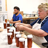 Robbie Gardisky, left, filling up 12 oz jars with honey and Terri Giles, vice president government relations Appalachian Headwaters, places labels on the lids at Camp Waldo in Hinton<br /> (Rick Barbero/The Register-Herald)
