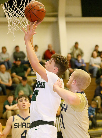 (Brad Davis/The Register-Herald) Wyoming East's Jacob Bishop drives to the basket as Shady Spring's Logan Cook defends Friday night in New Richmond.