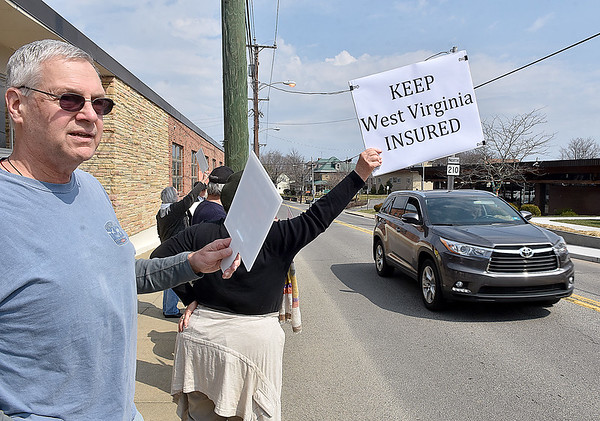 (Brad Davis/The Register-Herald) Beckley residents Bob Baker, left, and Sandra Wolf (holding sign) join fellow residents, doctors and healthcare advocates as they line the sidewalk outside of Senator Shelley Moore Capito's office at 220 North Kanawha Street protesting the looming potential repeal of the Affordable Care Act Friday afternoon.
