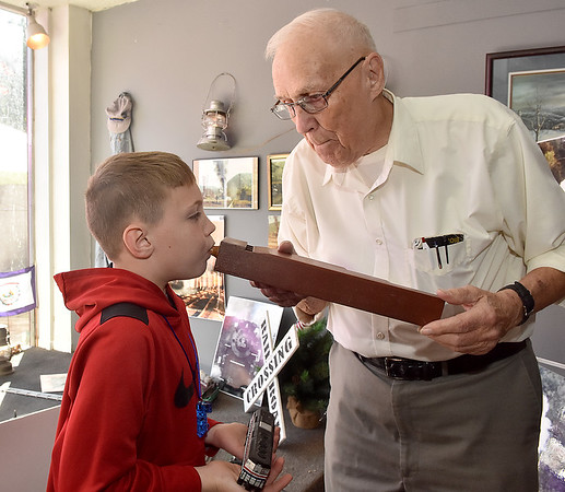 (Brad Davis/The Register-Herald) Hinton resident and longtime railroad photographer Curt Messer, right, gives eight-year-old Kentucky resident Owen Salyer the chance to experience the sound a 75-year-old, three-tone railroad whistle makes during Hinton Railroad Days Sunday afternoon.