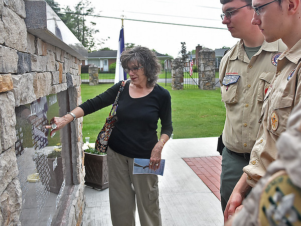 (Brad Davis/The Register-Herald) Area resident Carol Sullivan, left, holds back tears as she points out the name of her brother etched into the wall of the Huse Park monument to a group of young boy scouts following a Memorial Day candlelight vigil Sunday evening at Fayetteville's Huse Memorial Park. Sullivan's brother, Roger A. Castle, was killed in Vietnam February 24, 1967.