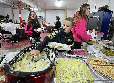 Brad Davis/The Register-Herald Ten-year-old Rhodell resident Dallas Austin, middle, helps himself to a hearty scoop of mashed potatoes during the town's annual Thanksgiving dinner Saturday night at the Rhodell Volunteer Fire Department.