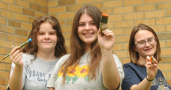 Shady Spring High School art students Madison Day, Sydney Harper, and Serenity Brooks play with the brushes they used to create murals for  the cafeteria of the school.  Jon C. Hancock/for The Register-Herald