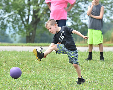 (Brad Davis/The Register-Herald) Six-year-old Bentley Rose crushes the ball to th outfield as he and fellow youths play kickball during Grandview Christian Church's Wacky Wednesday outdoor activity event at their property in Grandview where the old drag strip is.