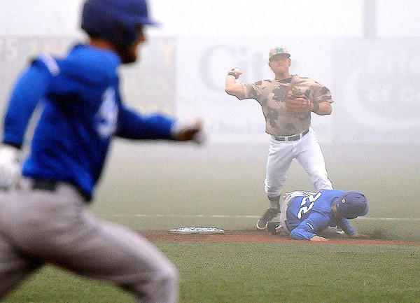 Brad Davis/The Register-Herald Middle Tennessee's Dustin Delgado (left foreground) hustles to first as teammate Kaleb King (#22) tries to take out Marshall second baseman Aaron Bossi as he turns a double play during a foggy Sunday afternoon at Linda K. Epling Stadium.