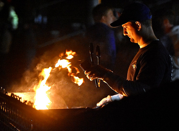 (Brad Davis/The Register-Herald) The lights kept going out at Indy, but the grillin' went on as Jamie Bolen flips burgers in the dark during the lighting delay Friday night in Coal City.