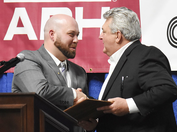 Jeff Miller, left, hands Greg Darby the award for the 2018 Community Service Award, during the 98th annual Beckley-Raleigh County Chamber of Commerce Annual Dinner at the convention center in Beckley Friday.(Chris Jackson/The Register-Herald)