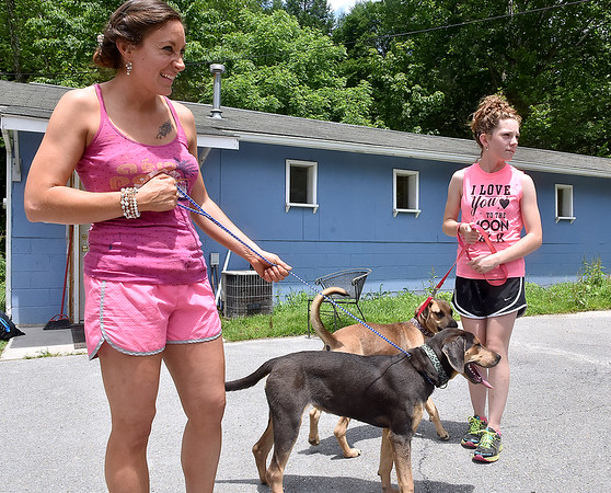 (Brad Davis/The Register-Herald) Fayette County Humane Society board member Mary Moses, left, and her daughter Ellie Groves take a pair a recently dropped off dogs, suspected of being displaced by the flooding, for a walk Sunday afternoon at the animal shelter near Fayetteville.