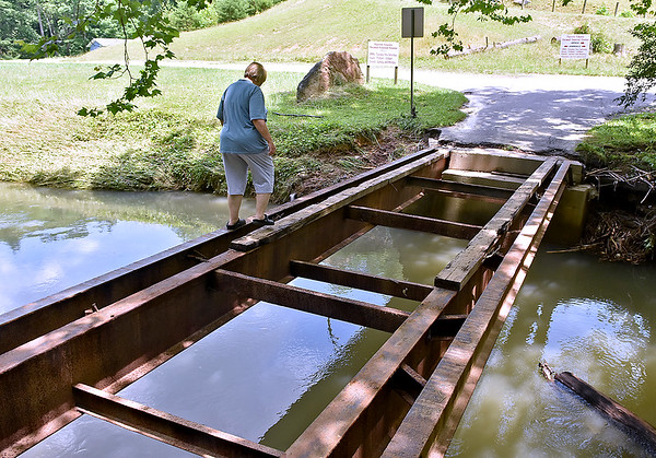 (Brad Davis/The Register-Herald) Volunteer Anna Bennett carefully crosses Laurel Creek using the the steel frame of the bridge leftover from flooding in the area on her way to the Fayette County Animal Shelter Sunday afternoon. Unless you'd want to wade through the water, this is currently the only way to access the shelter until the bridge is rebuilt.