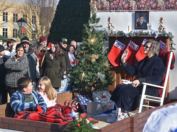"""(Brad Davis/The Register-Herald) Members of the New Life Baptist Church in White Oak wave to the crowd from their """"Home for the Holidays"""" float during the Beckley Christmas Parade Saturday morning."""