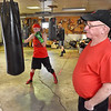 (Brad Davis/The Register-Herald) Boxing trainer Carl Murdock runs his garage gym at his Mount Hope home as Amber Sweeney (near bag) and Bobby Belcher (far bag), two of a handful of Beckley Toughman Contest fighters in his stable this year, put in work Monday evening. The 70-year-old Murdock is widely considered to be one of the most effective at grooming local scrappers into polished boxers that win matches, with his Mount Hope Boxing Club producing some 40 champions male and female over a 30 plus year period. The walls of his garage gym are parts local boxing museum, hall of fame and champions' club. Each fighter who trains with him aspires to be on his wall one day.