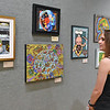 (Brad Davis/The Register-Herald) Visiting California resident Sarah Hempton admires culinary-themed works Saturday evening during the opening reception for Good Enough to Eat: Please Don't Eat the Art, the newest juried art exhibition at Tamarack that will be on display until September 23.