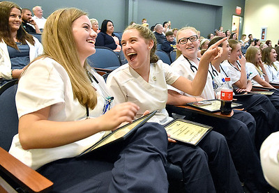 (Brad Davis/The Register-Herald) Graduates share several laughs as they watch a slideshow full of photos - and outtakes - from their time as participants in the first Southern West Virginia Junior Nursing Academy during the closing moments of a ceremony Thursday evening at the Erma Byrd Higher Education Center.