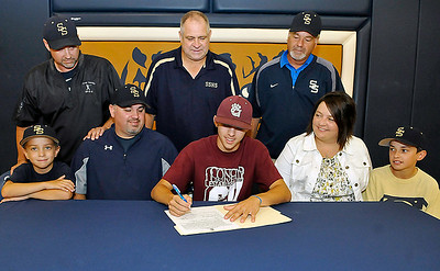 Shady Spring standout athlete Jordan Meadows signs a letter of intent to play baseball at Concord University surrounded by coaches and family Monday afternoon in the Tigers' gymnasium. Joining him at the table are his little brothers Jason (far right) and Jacob (far left), his parents Sheila and Scotty (left of Jordan), Shady Spring Athletic Director Steve Clark (back row middle) and baseball coaches Darrell Frasier (back row left) and James Sears (back row right). Brad Davis/The Register-Herald