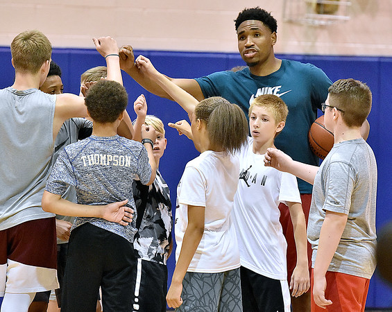 (Brad Davis/The Register-Herald) Former West Virginia Mountaineers player Kevin Jones (2008-2012) congratulates a group of young area players after a good series of skill-building drills during the Fundamentals with coach Herbie Brooks basketball camp Saturday afternoon at Beckley-Stratton Middle School. Jones has been playing professionally in Europe since his Mountaineer days, spending last season with Nanteere 92 of the LNB Pro A league in France.